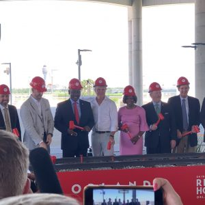 VIPs in hard hats posing for a picture at the Virgin Trains USA Groundbreaking